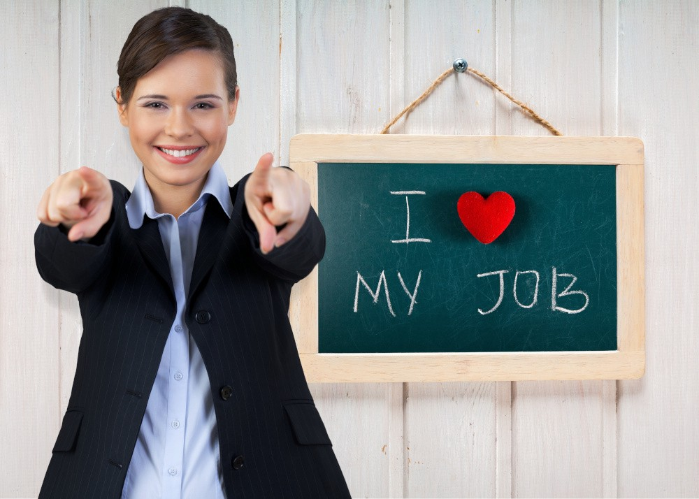 A woman and a I love my job sign