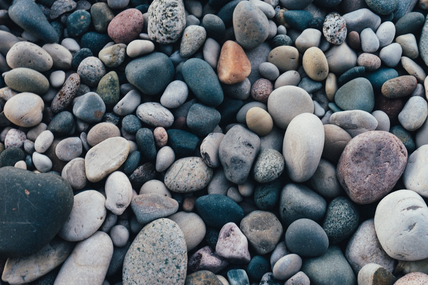 A pile of soft, rounded and speckled weathered stones and pebbles