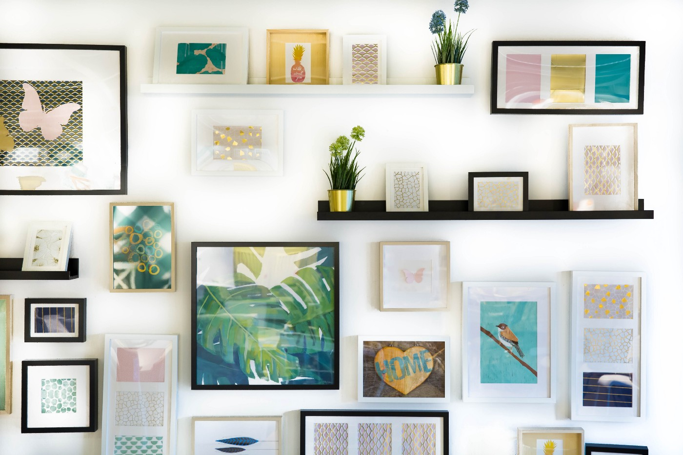 pictures and shelves of decorative objects arranged on a wall