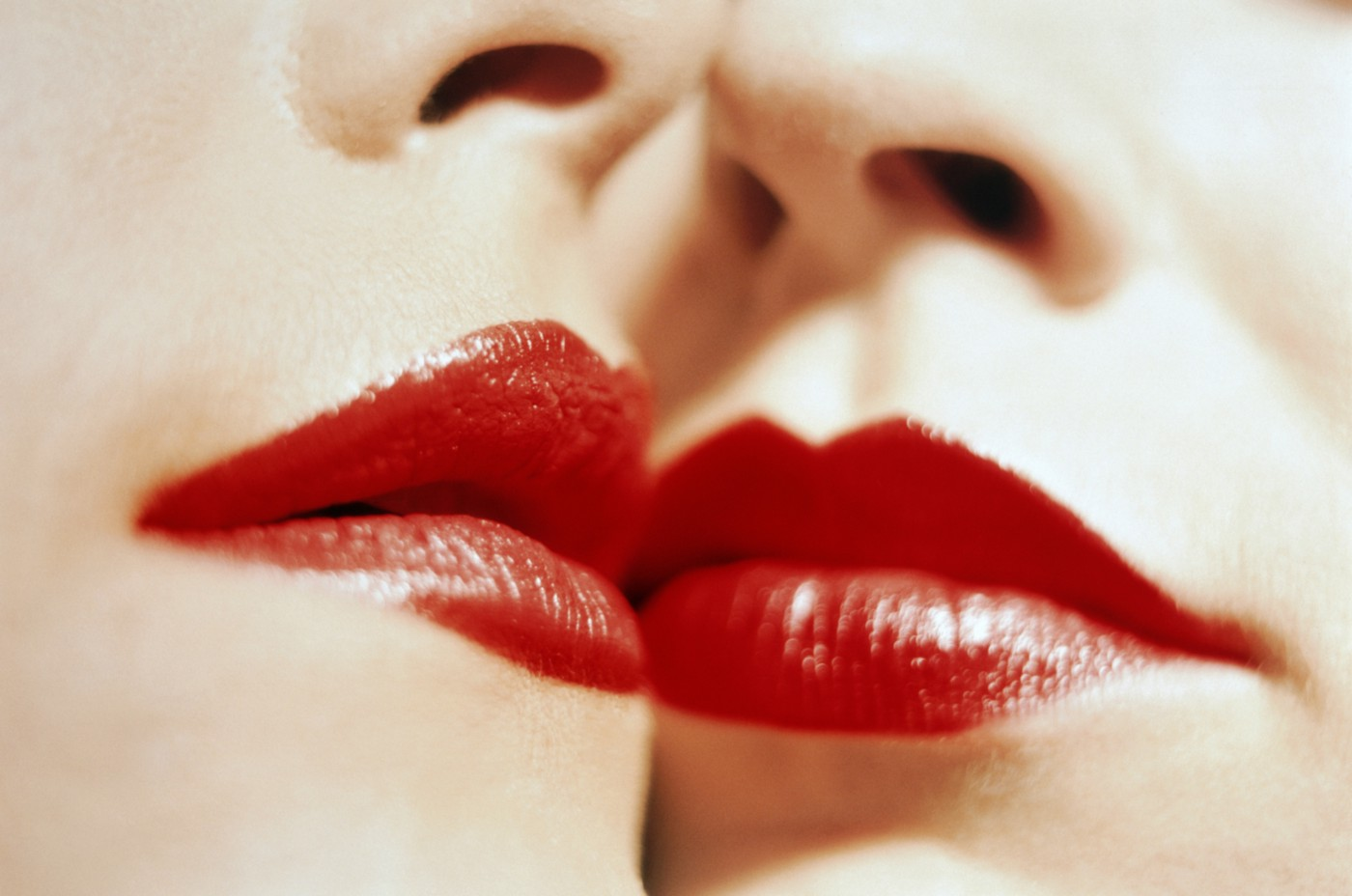 A closeup photo of two women with red lipstick with their faces touching.