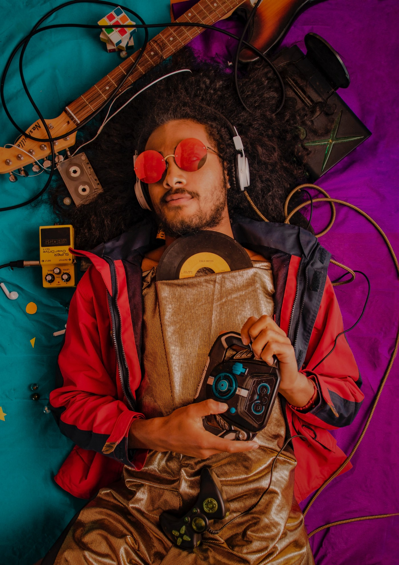 Person with dreads & facial hair wearing pink, round glasses amidst by music technology & holding vinyl & game controllers