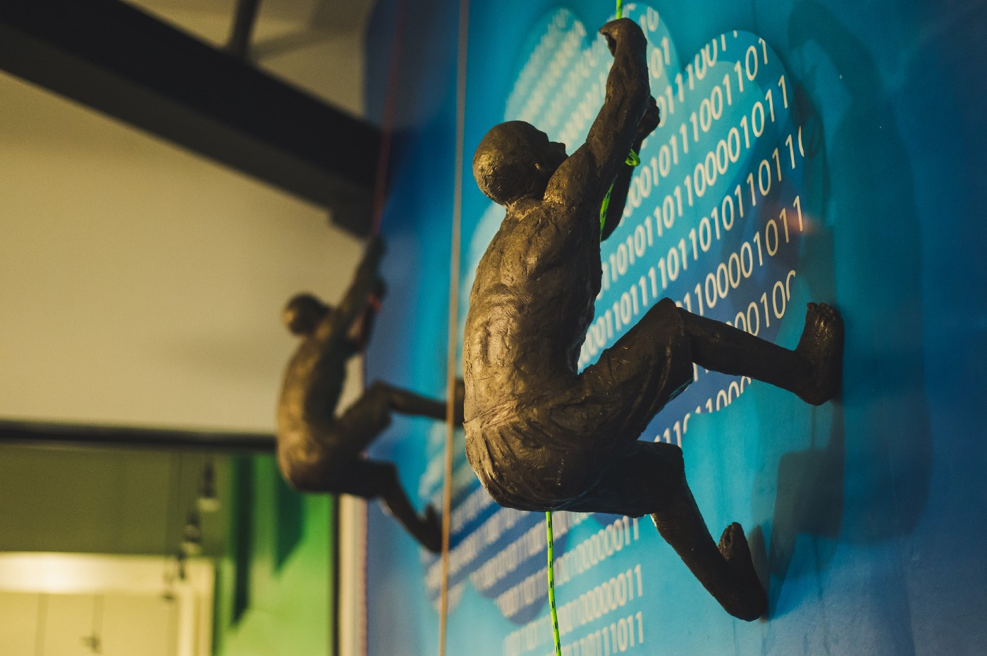Two bronze figurine men climbing a wall with binary code printed on it.
