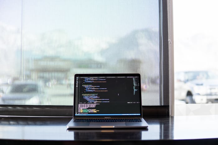 Clean, minimal workspace setup with laptop displaying code in front of a window.