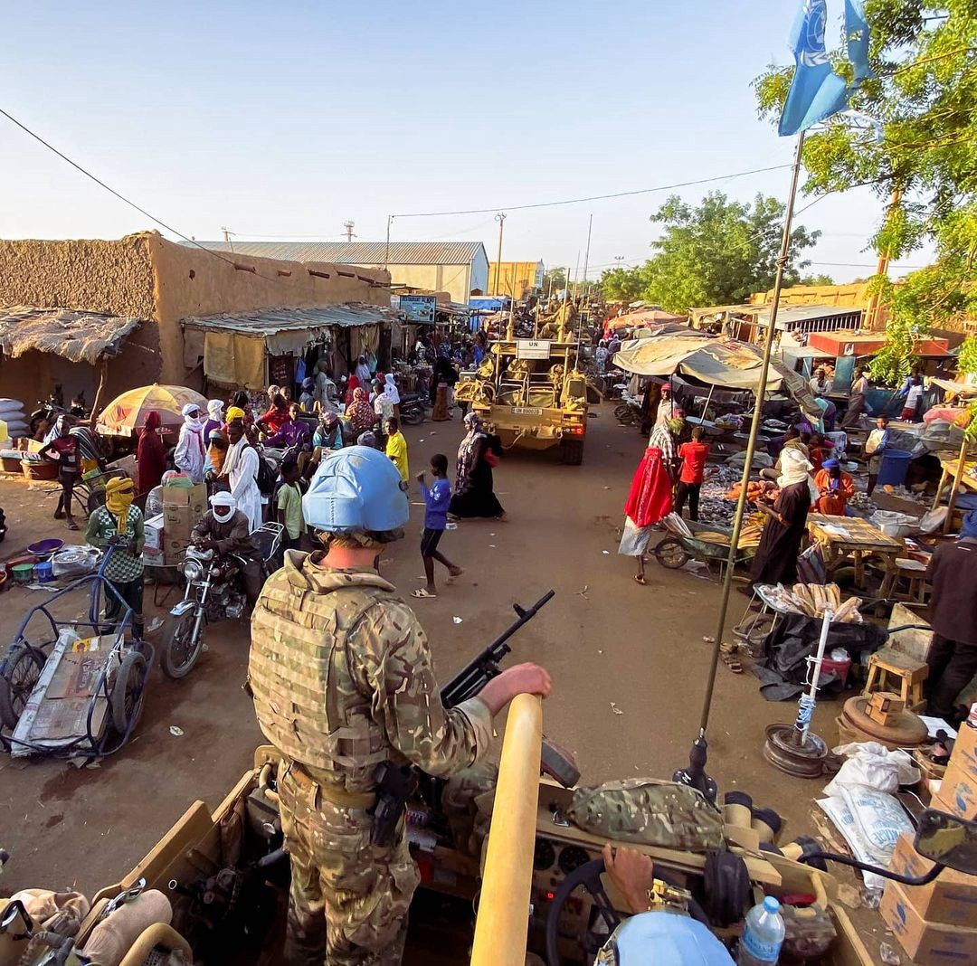 British peacekeepers drive through a village during market day.