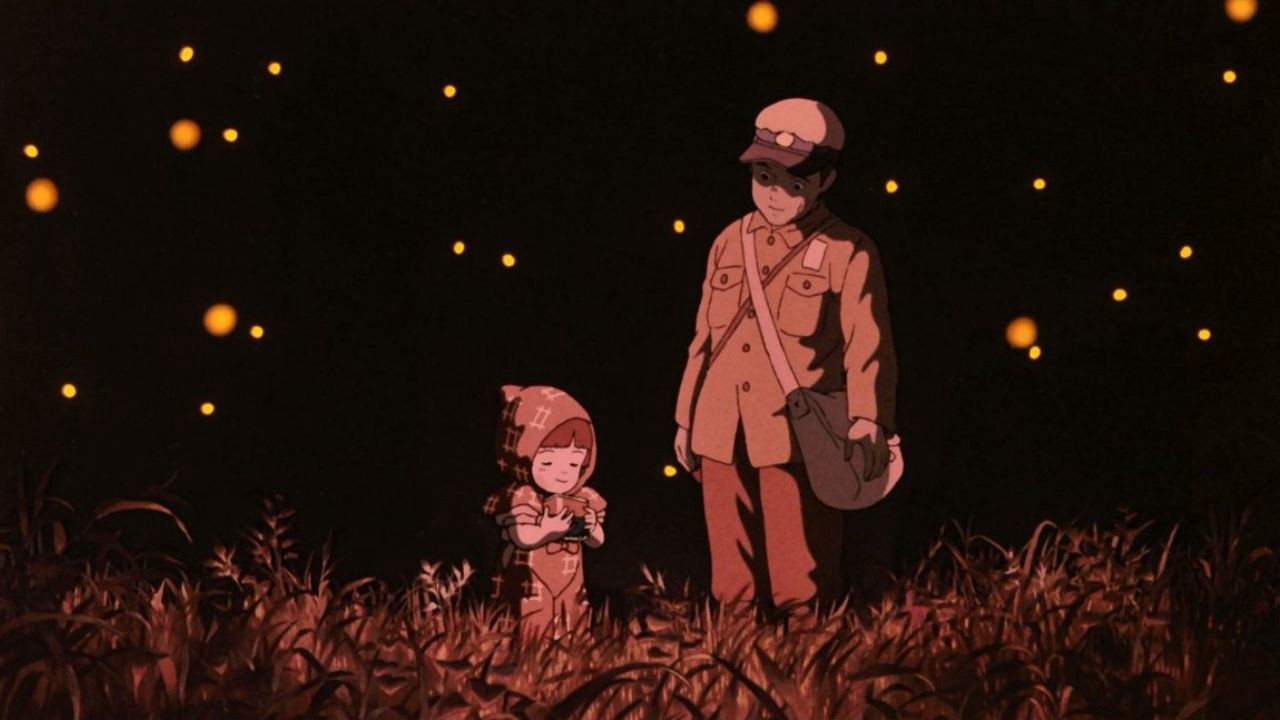 A young girl, Setsuko, wearing a dress, and her older brother Seita, wearing military-like clothing. They're standing in a field at night, illuminated by the dim glow of fireflies all around them.