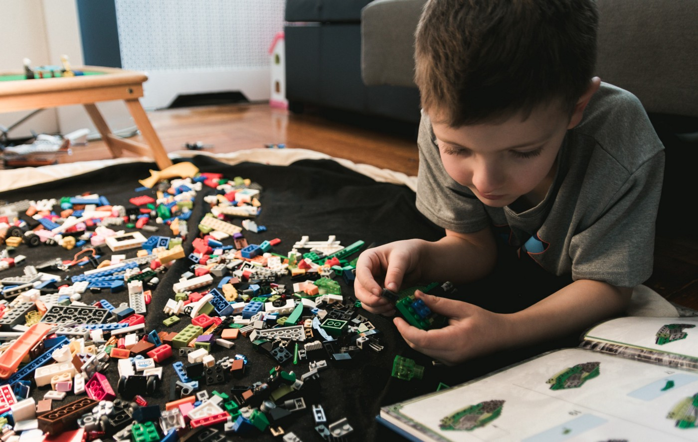 Young boy looking at instructions for a lego set