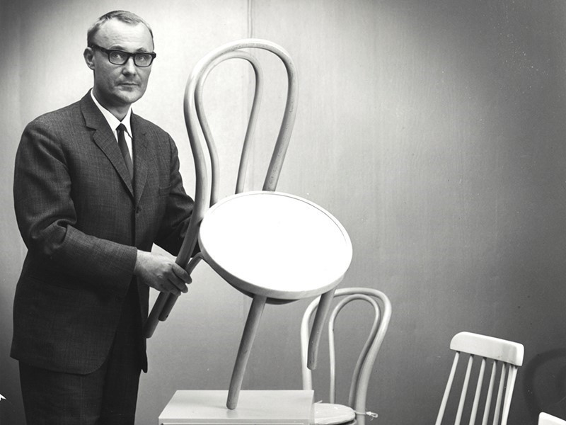 Old image of IKEA founder holding a chair