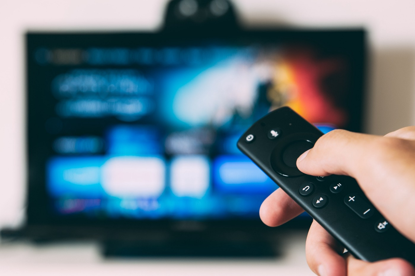 Hand holding a television remote. The television is blurred in the background.