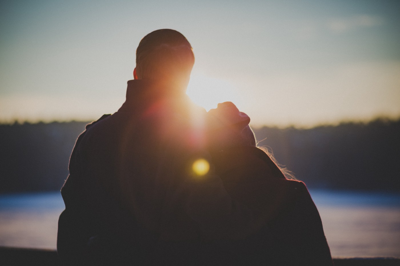 A photo of the back of a couple in a wintery nature landscape.