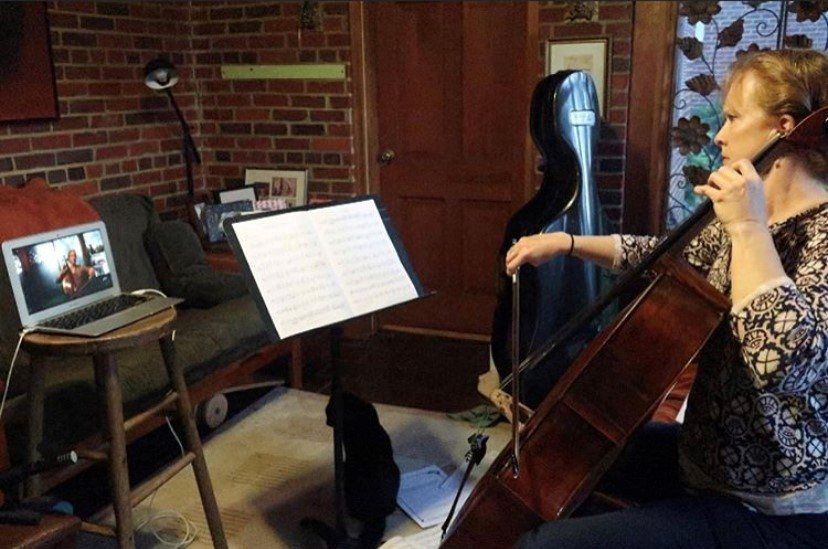 A cellist records her performance on a laptop