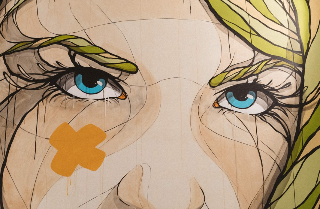 Graffiti art of blonde woman with blue eyes with an orange x on left cheek