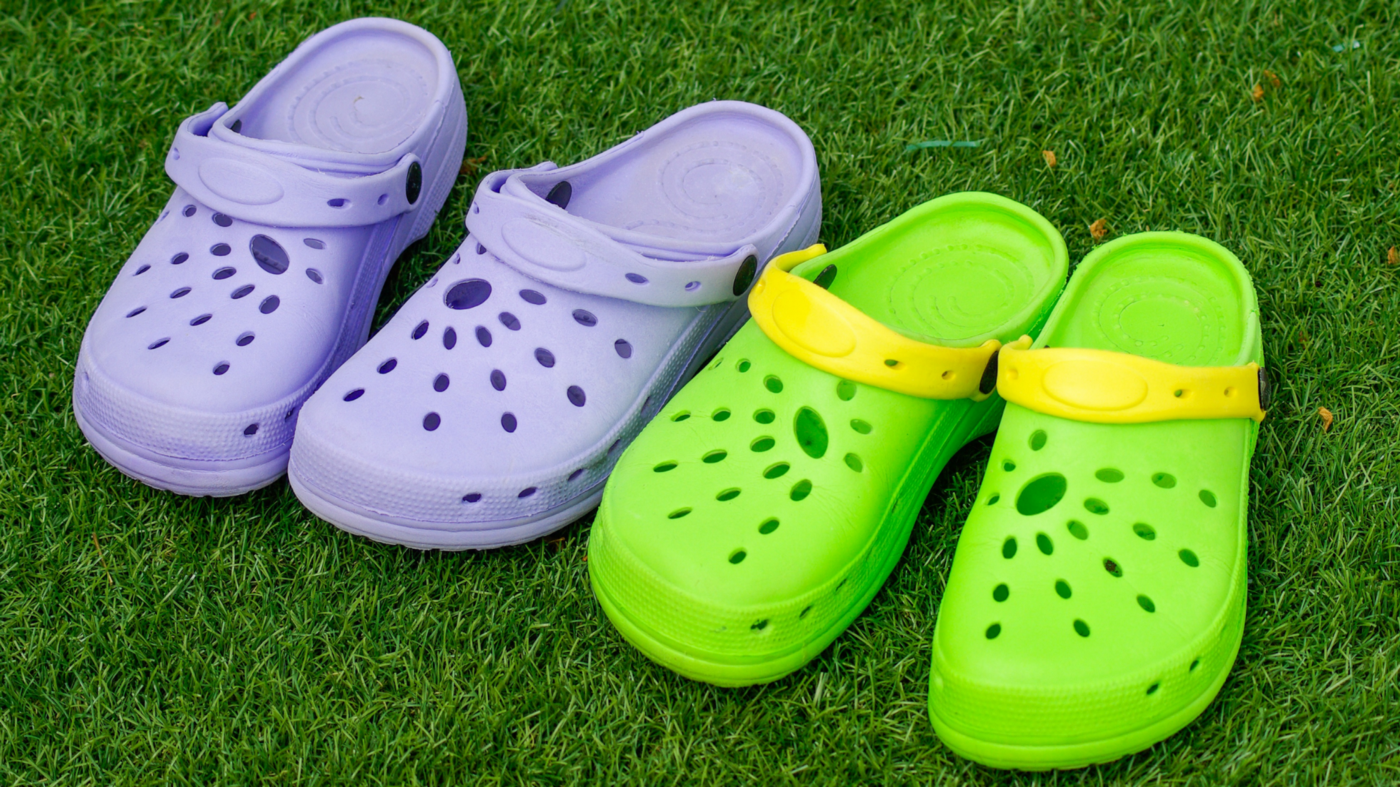 Pair of purple and green crocs on some grass