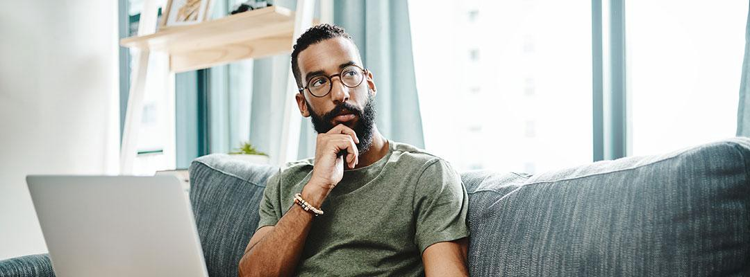 Image of black man pondering something while sitting on the couch