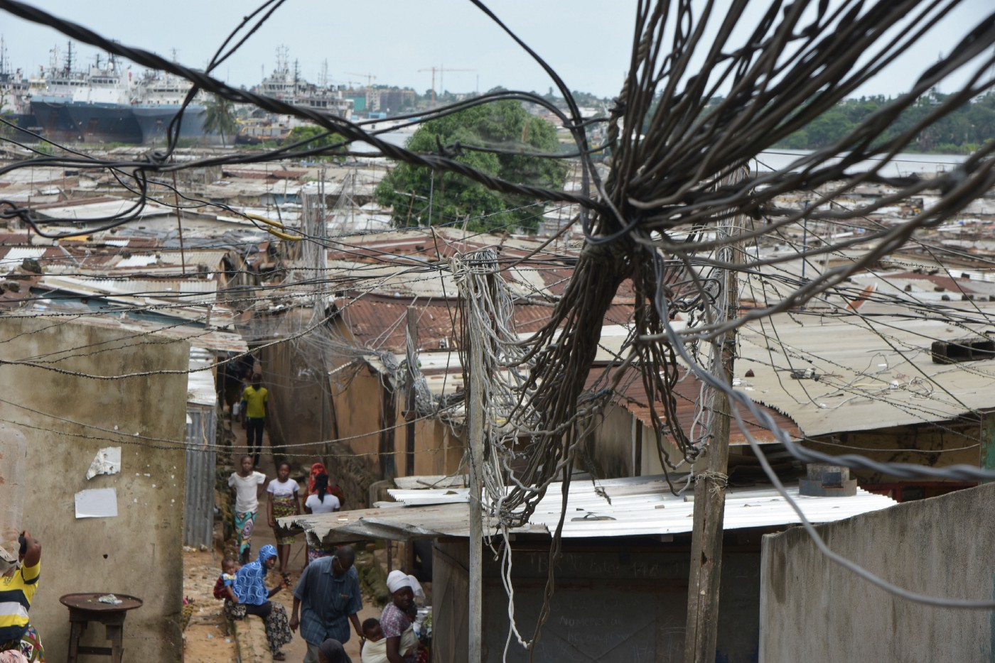People walk under electric wires connected above roofs in a district of Abidjan, Côte d'Ivoire on June 1, 2019.