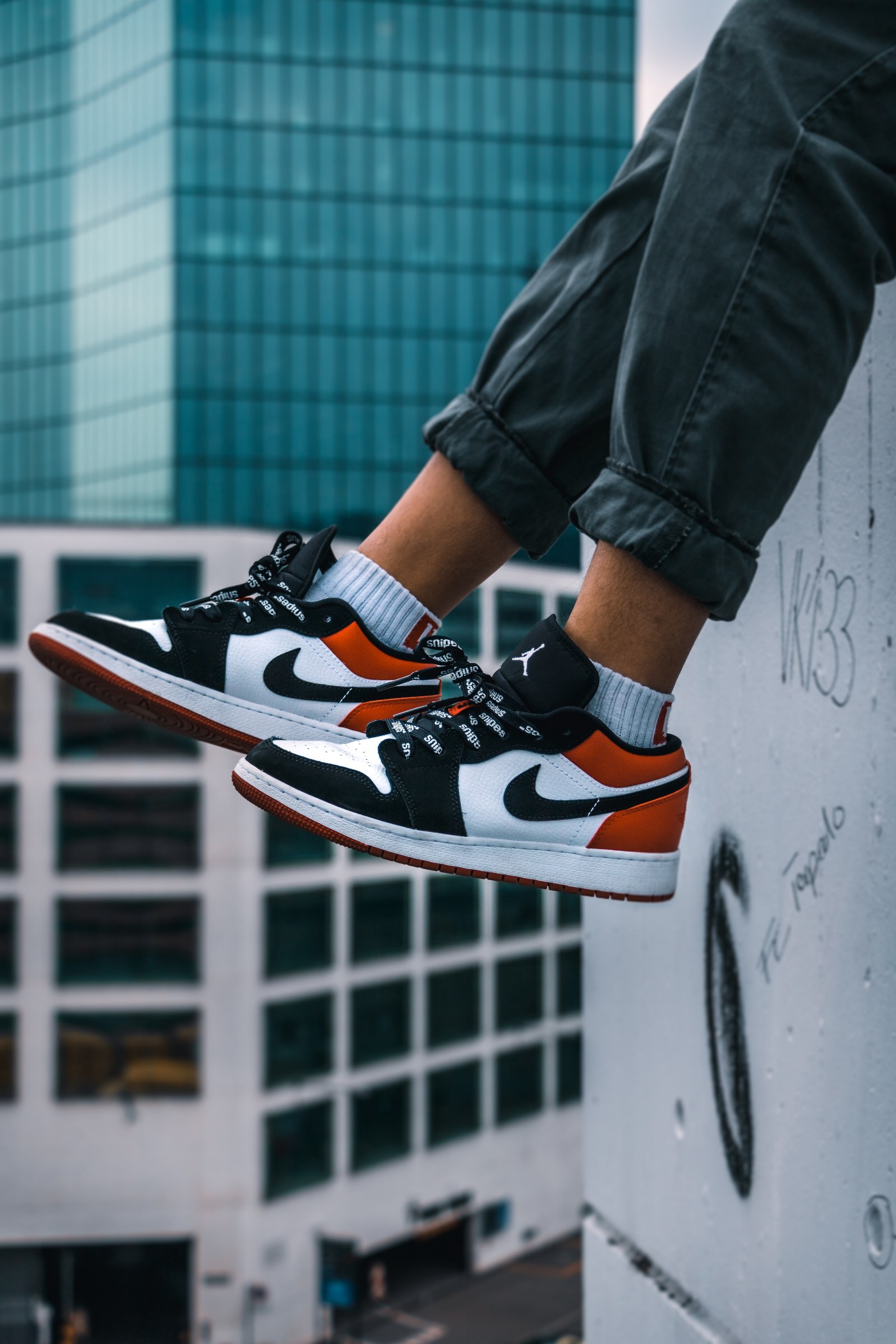 Person with legs dangling from a ledge wearing Nike sneakers