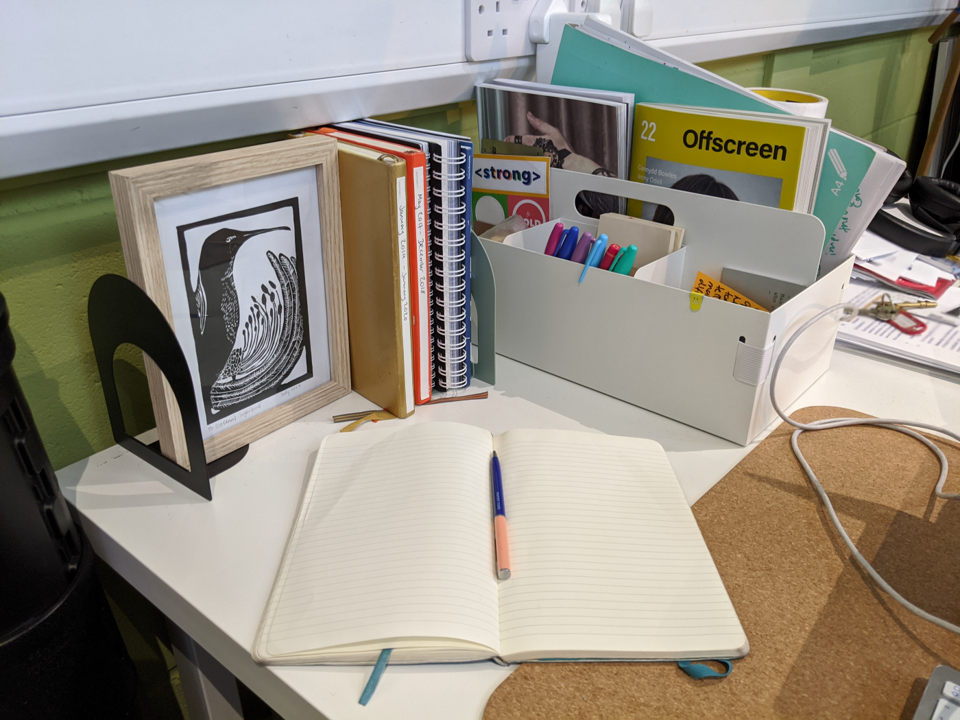 A desk with a notebook and pen, some books, a picture and a toolbox full of stationery.