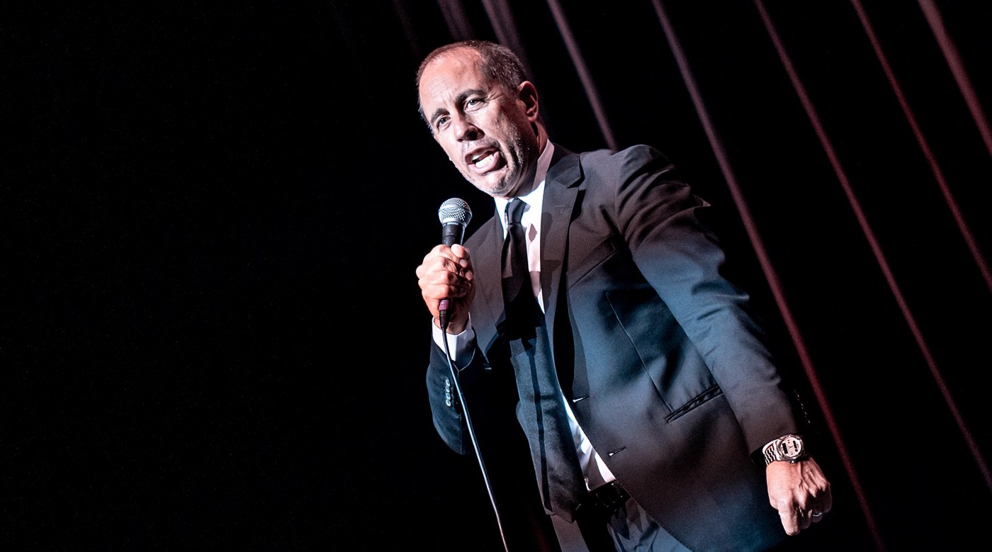 Comedian Jerry Seinfeld holds a microphone and entertains an audience at the Eventim Apollo in Hammersmith, London, UK on July 12, 2019. (Source: Wikimedia Commons)