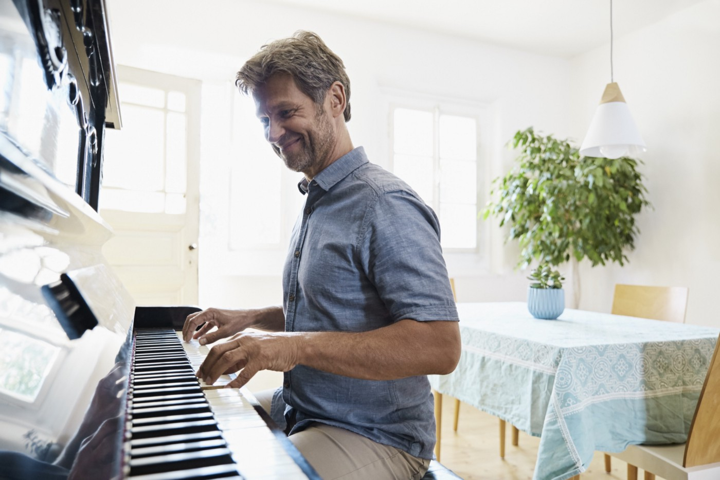 A man practices playing the piano at home.