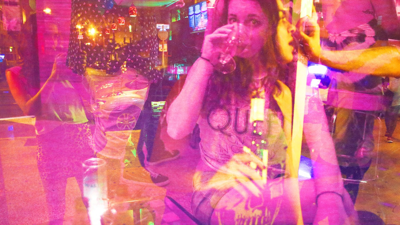 A double exposure depicting the author drinking a cocktail, staring into the camera, while another version of her takes a picture of the scene to the left. The image showing through from underneath her is a woman holding a beer, talking to someone outside the frame.