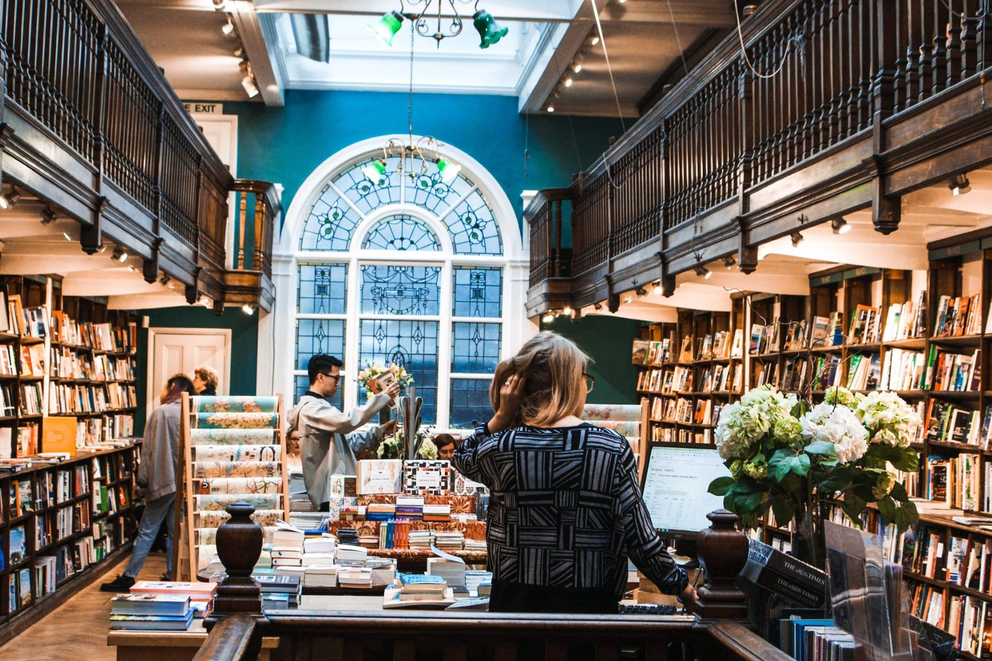 Inside a bookstore with balconies and a large stained glass window. Customers look around.