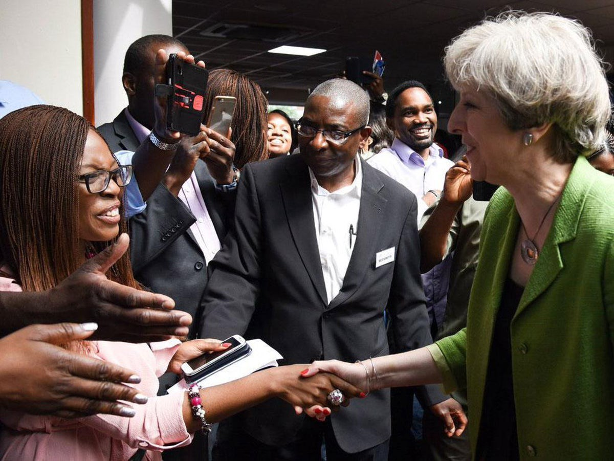 Former Prime Minister Theresa May shaking hands with Jesus House representatives, with press surrounding them.