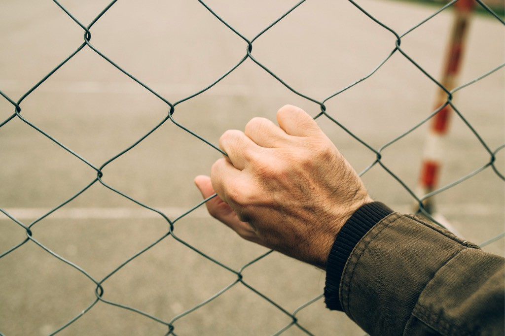 man's hand holding a chain link fence