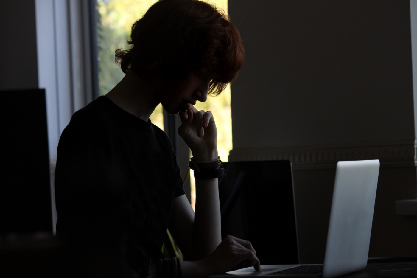 Dark image of a boy on his laptop.