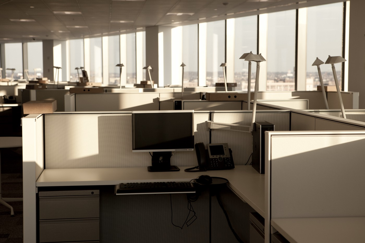 An office with rows of empty cubicles. Desks are cleared out, with natural sunlight shining in from the windows.