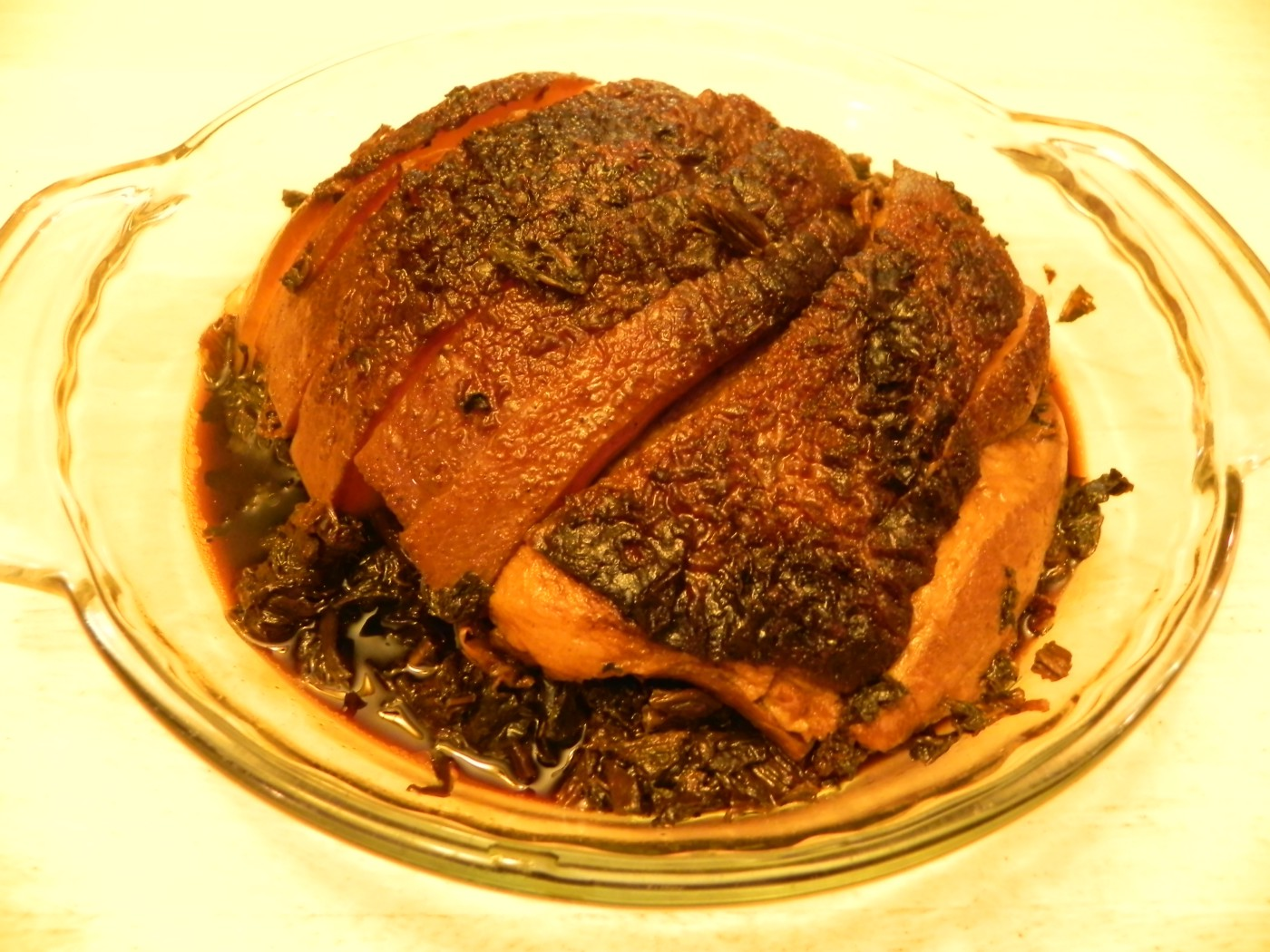 Roasted pork belly with dried vegetables sits on a glass plate