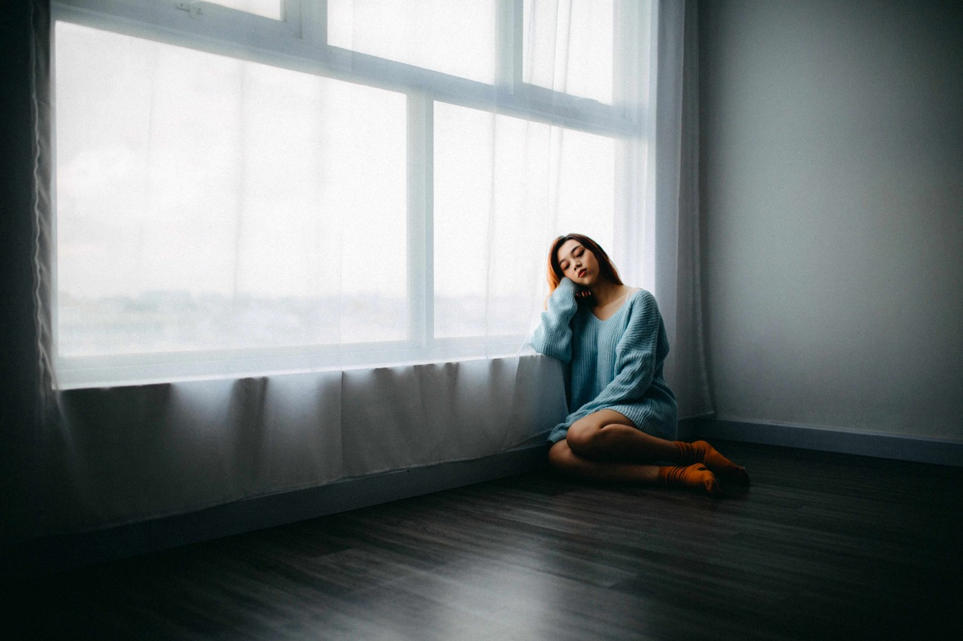 Woman sitting on the floor by a window, looking glum.