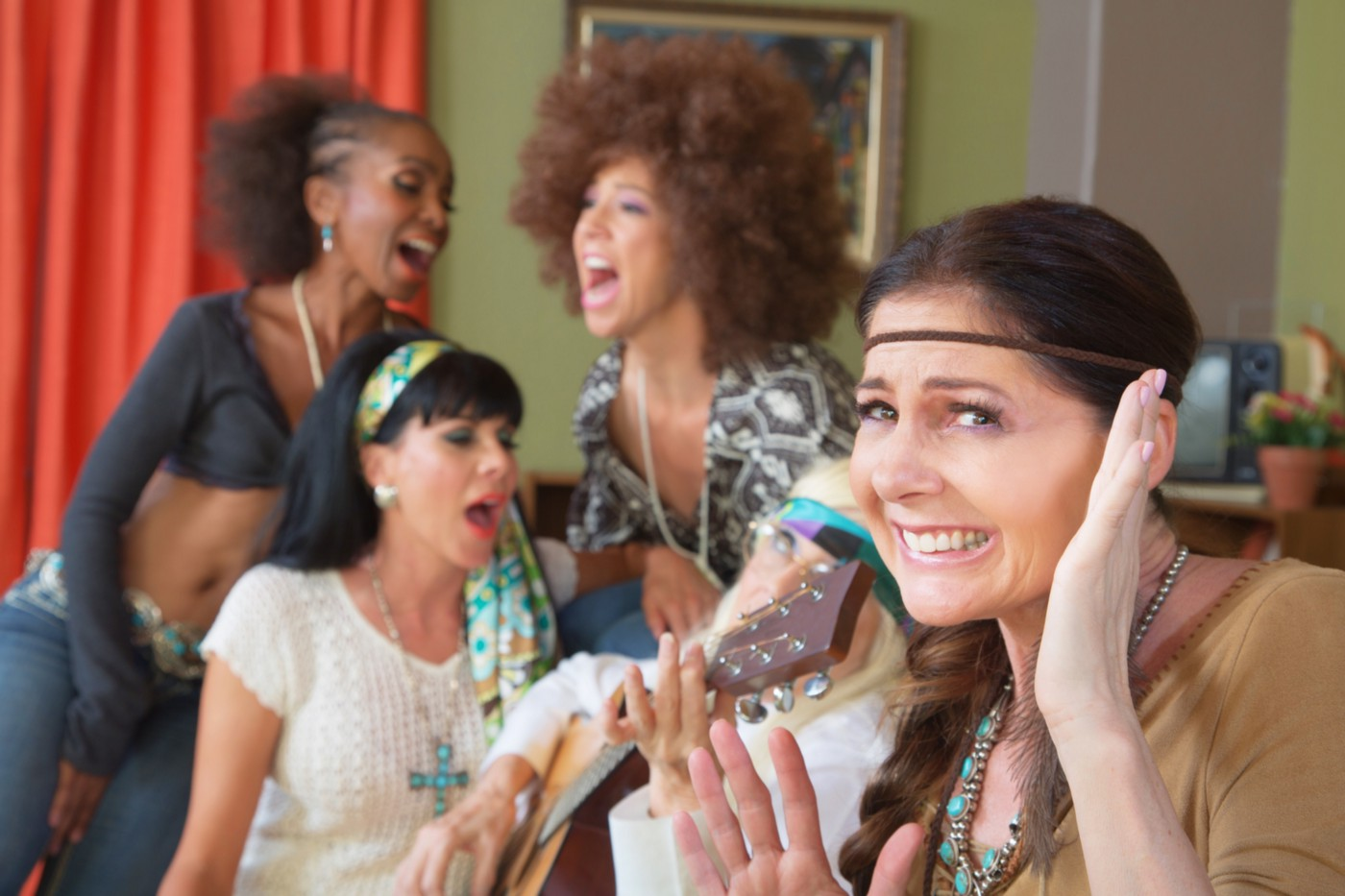 Woman in hippie-style costume smiling awkwardly as three women sing behind her