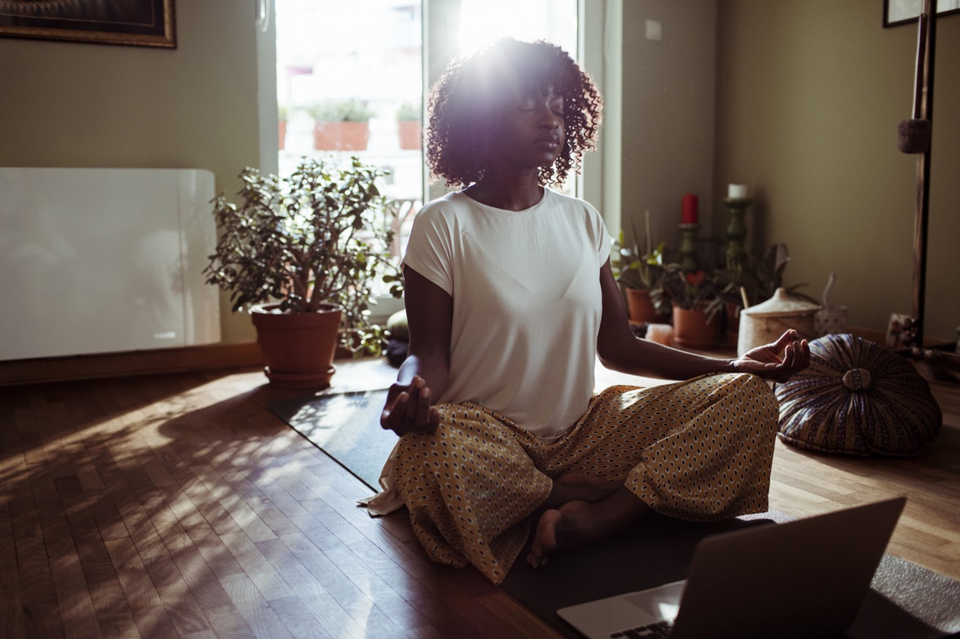 Black woman meditating in the living room.