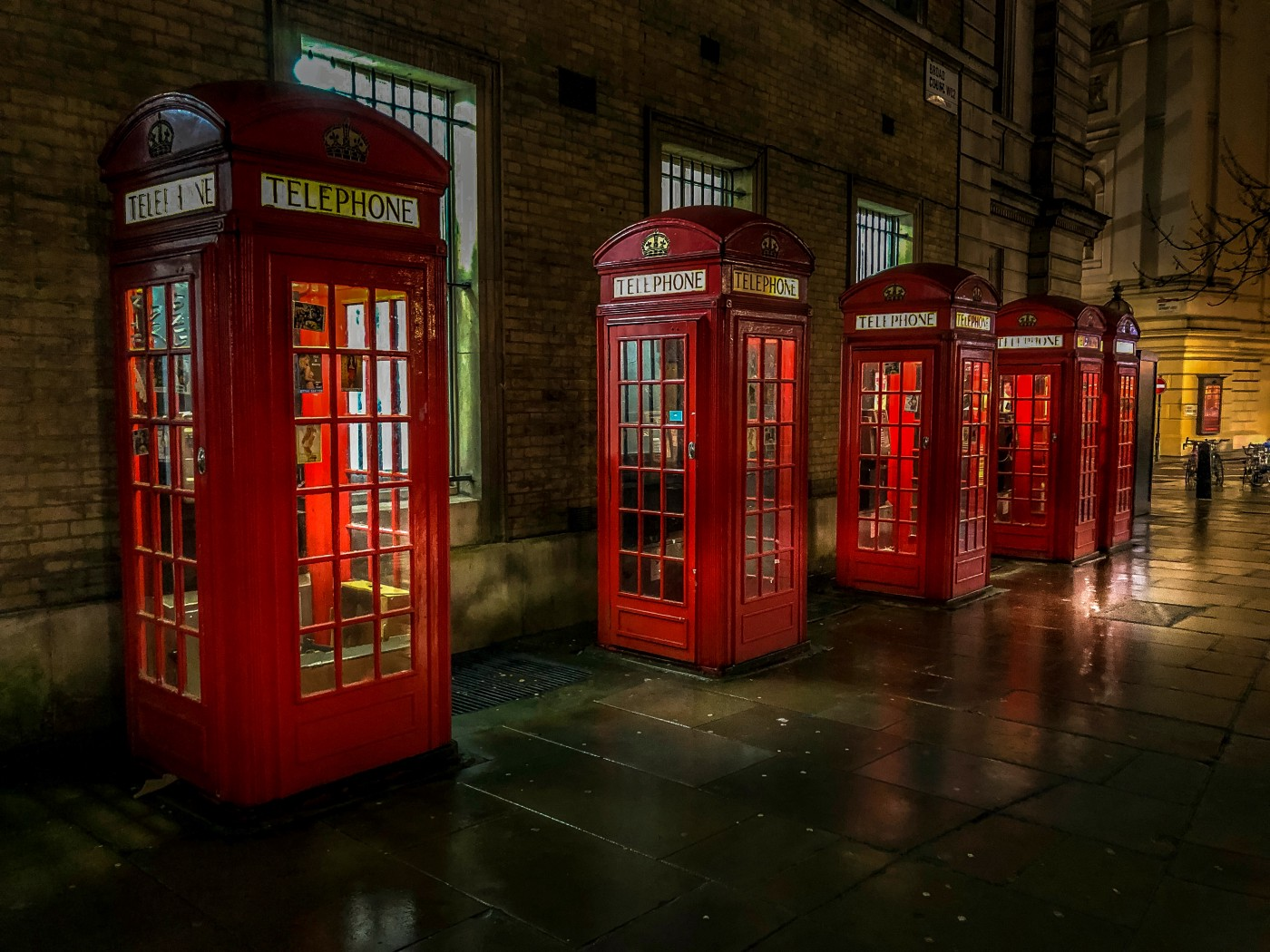 a row of red British telephone booths (call boxes) along a street