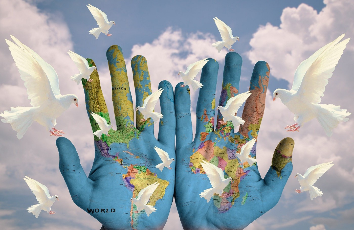 Pair of open hands painted with map of the continents as doves fly above them in symbol of peace.