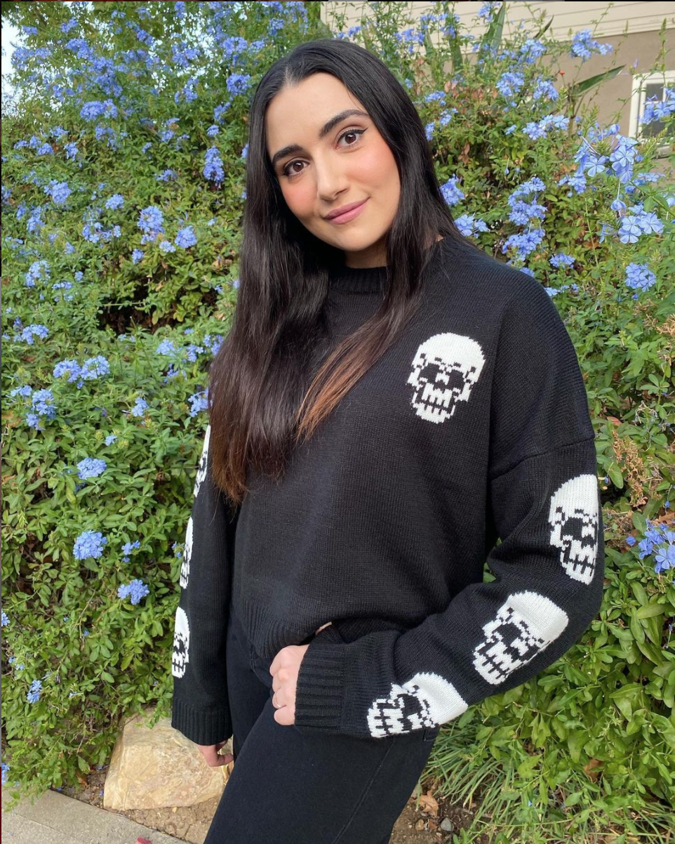 Photo of lifestyle, beauty, and fashion YouTuber Safiya Nygaard, wearing a black sweater with white skulls. She is standing with her head tilted, posed against a shrub with light blue flowers. She has long hair and is smiling.