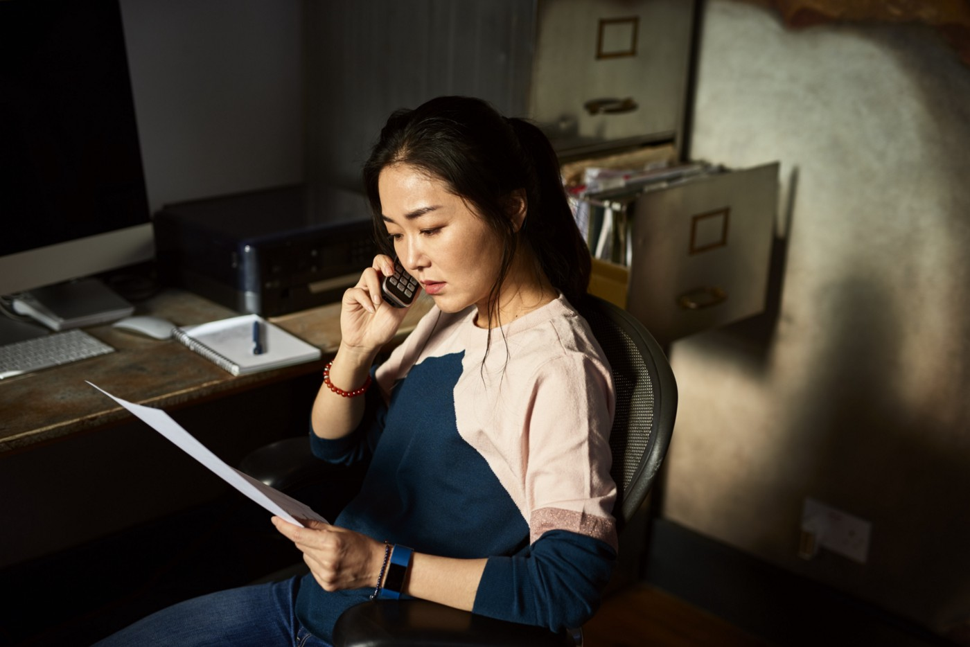 Woman on the phone while holding a piece of paper.
