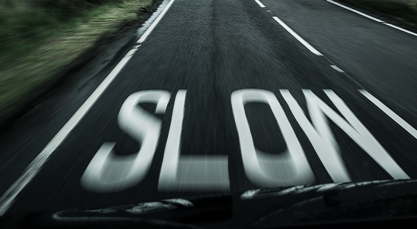 "View from a fast-moving car, ""slow"" painted on road"