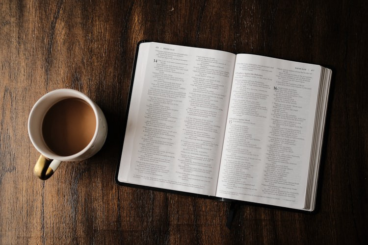 A cup of coffee sitting by an open book.
