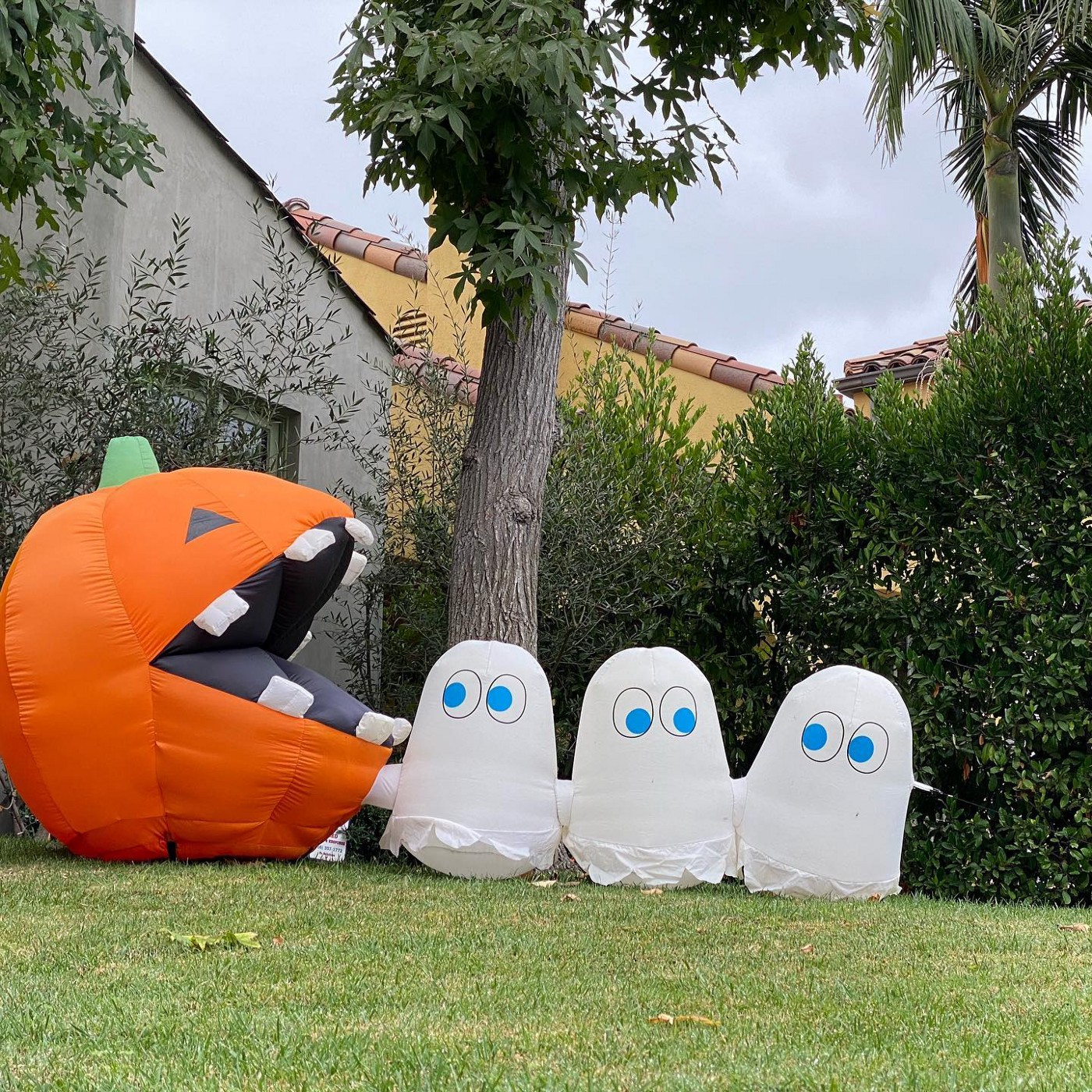 Inflatable Pac-Man-themed halloween yard decoration of a large orange chomping pumpkin chasing three fleeing ghosts.