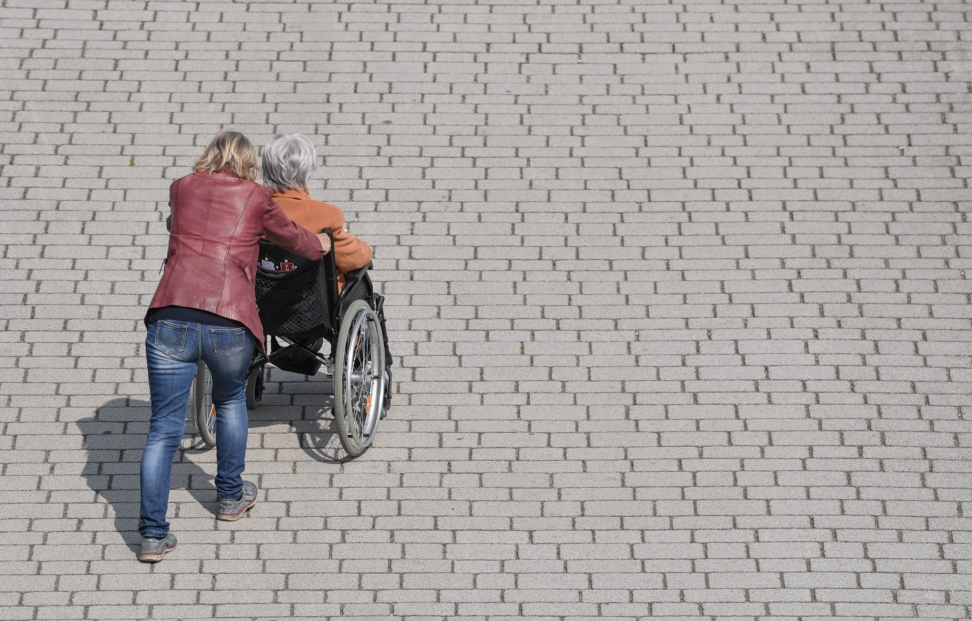 A woman pushes an elderly woman in a wheelchair across a sidewalk.