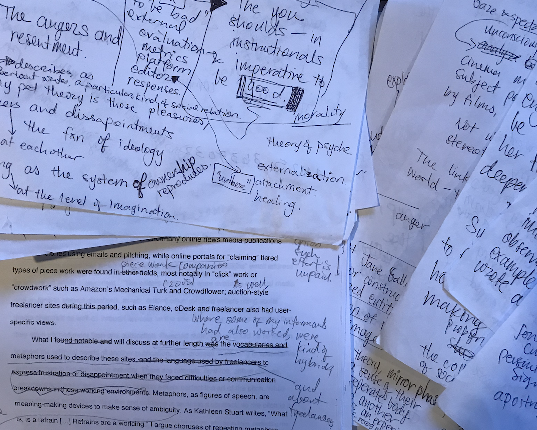 Papers with typed words, handwriting in margins.