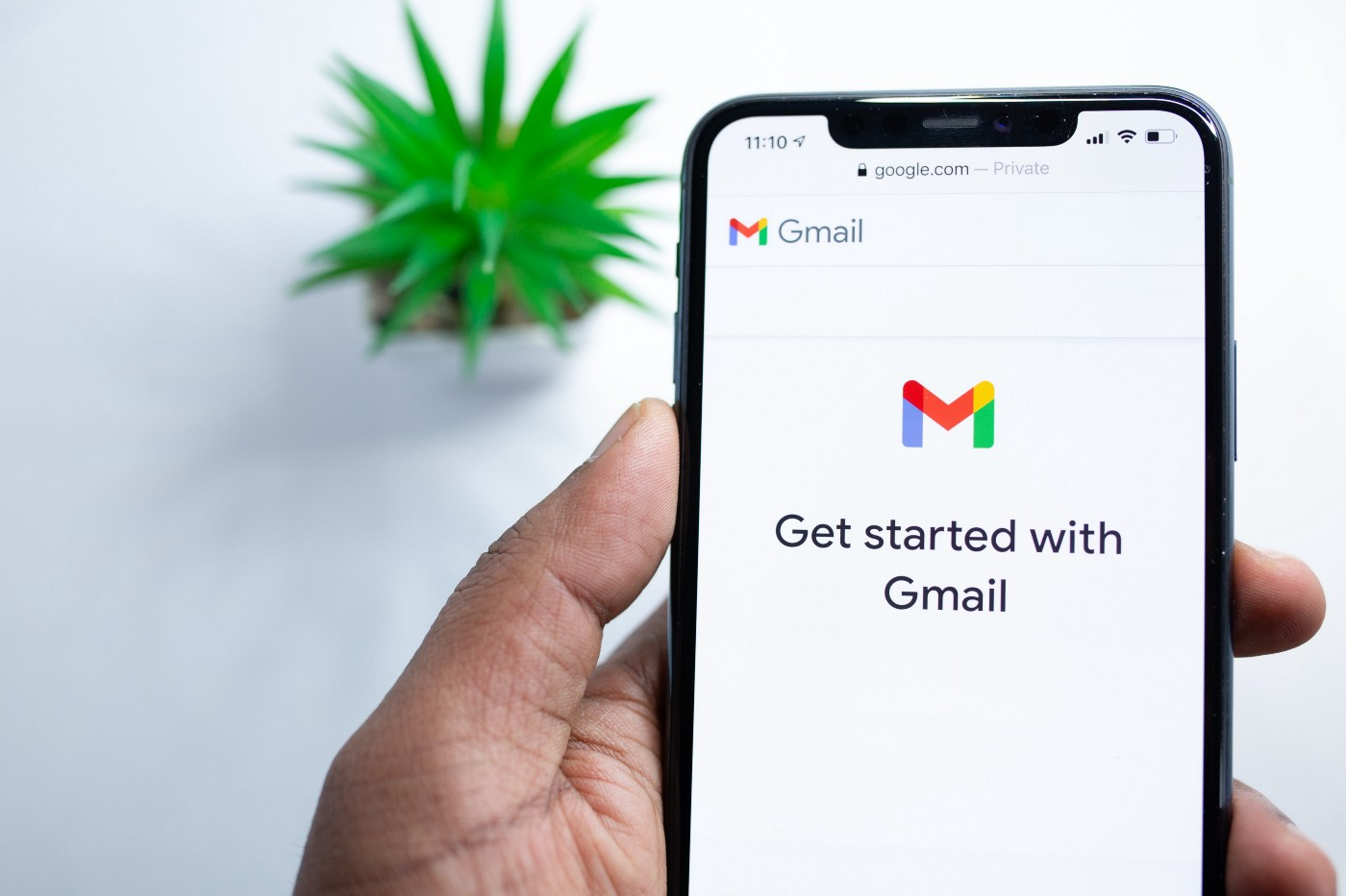 """a hand holding a phone showing the Gmail screen """"get started with Gmail"""""""