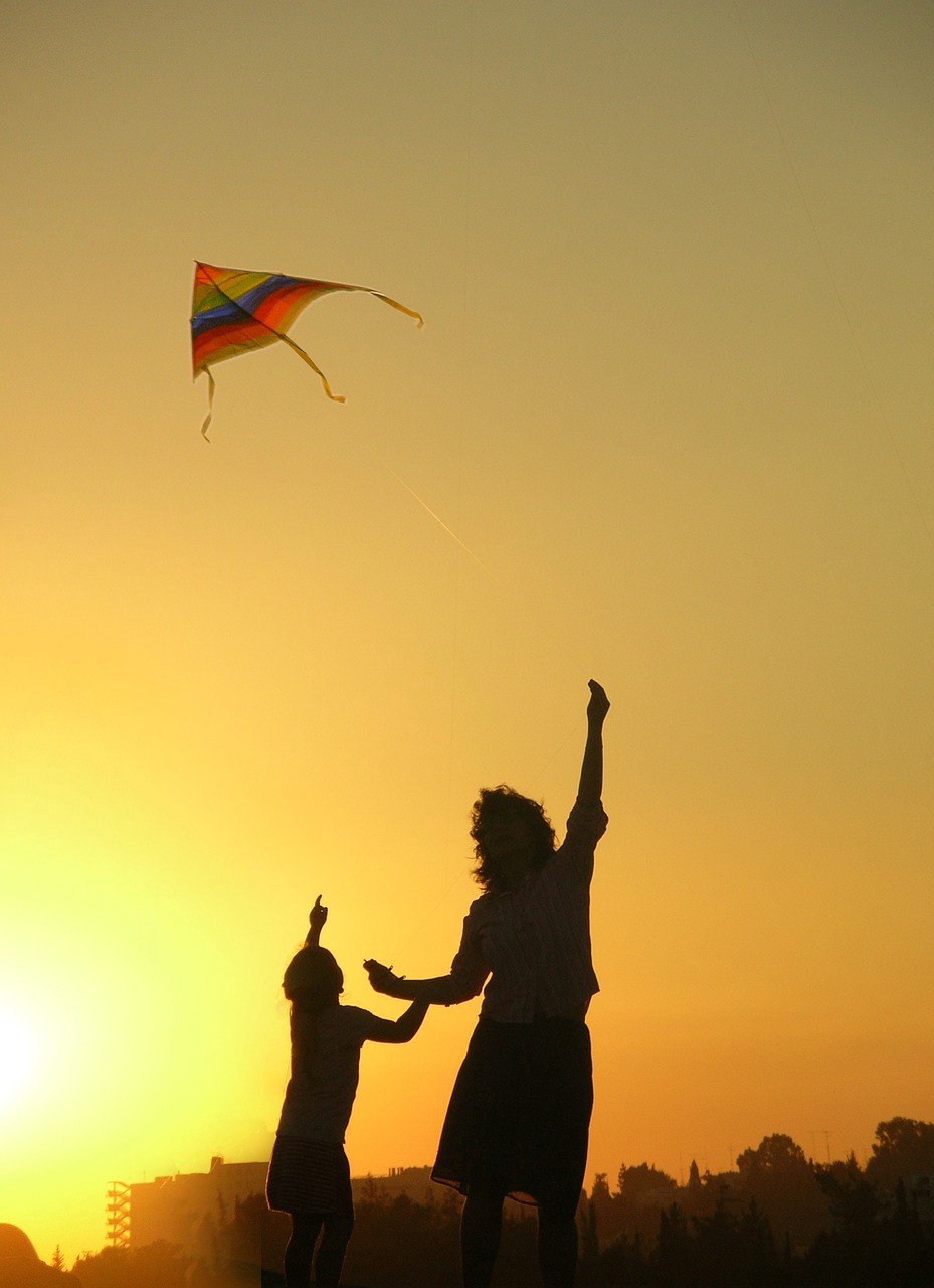 Silhouette of woman and child flying a rainbow kite against golden sky