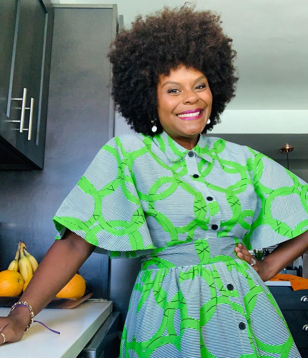 Tabitha Brown posing in a kitchen while wearing a bold graphic print dress.