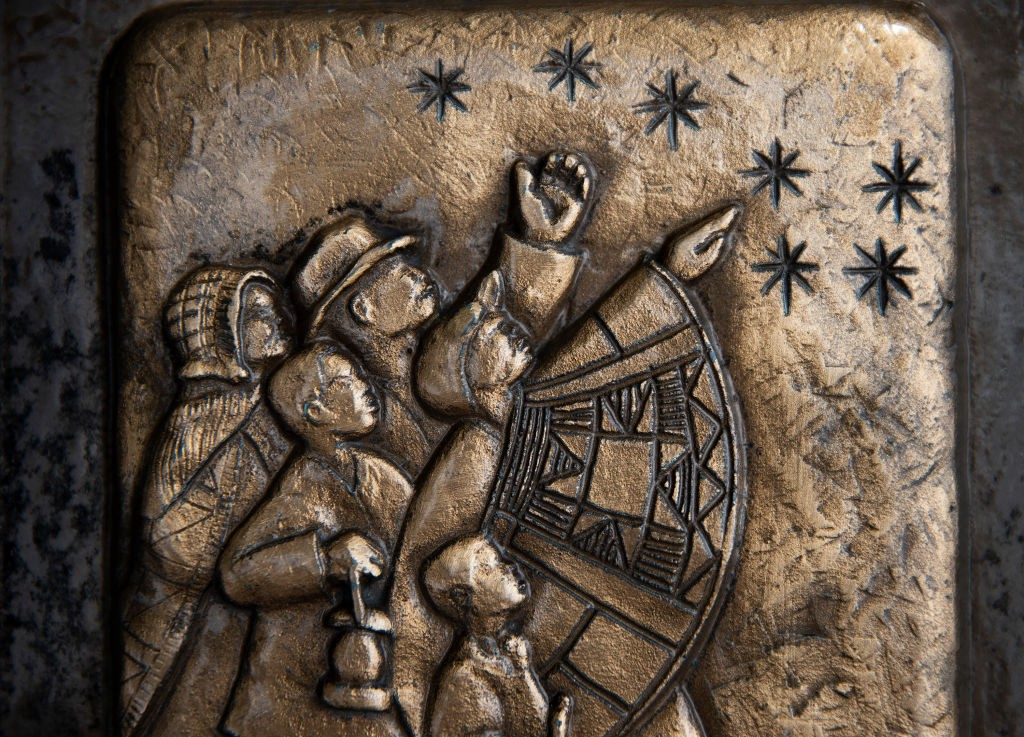 A closeup of a Freedom Trail marker that shows enslaved people guided by stars at night on their way to freedom.