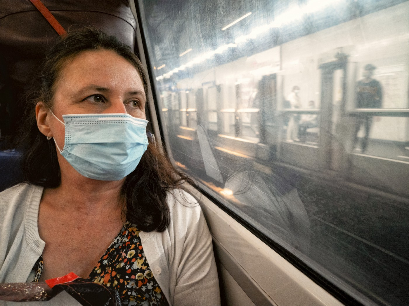 Woman riding train while wearing a face mask.