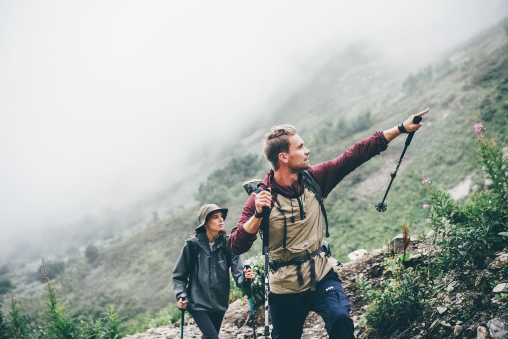 A photo of two people hiking on a mountain.