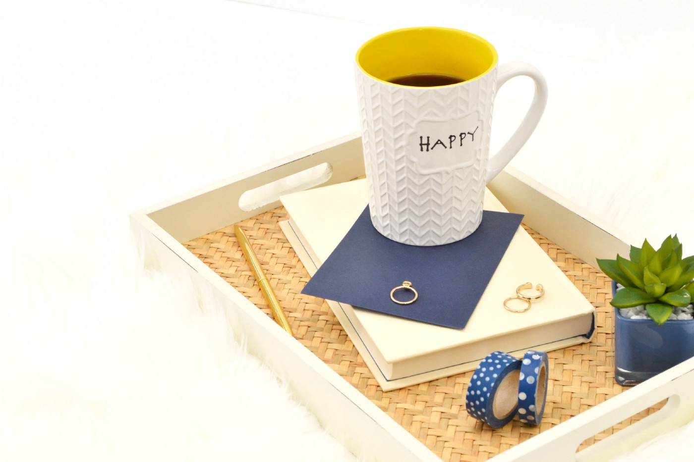"""A book with washi tape, wedding rings and a """"happy"""" mug in a tray."""