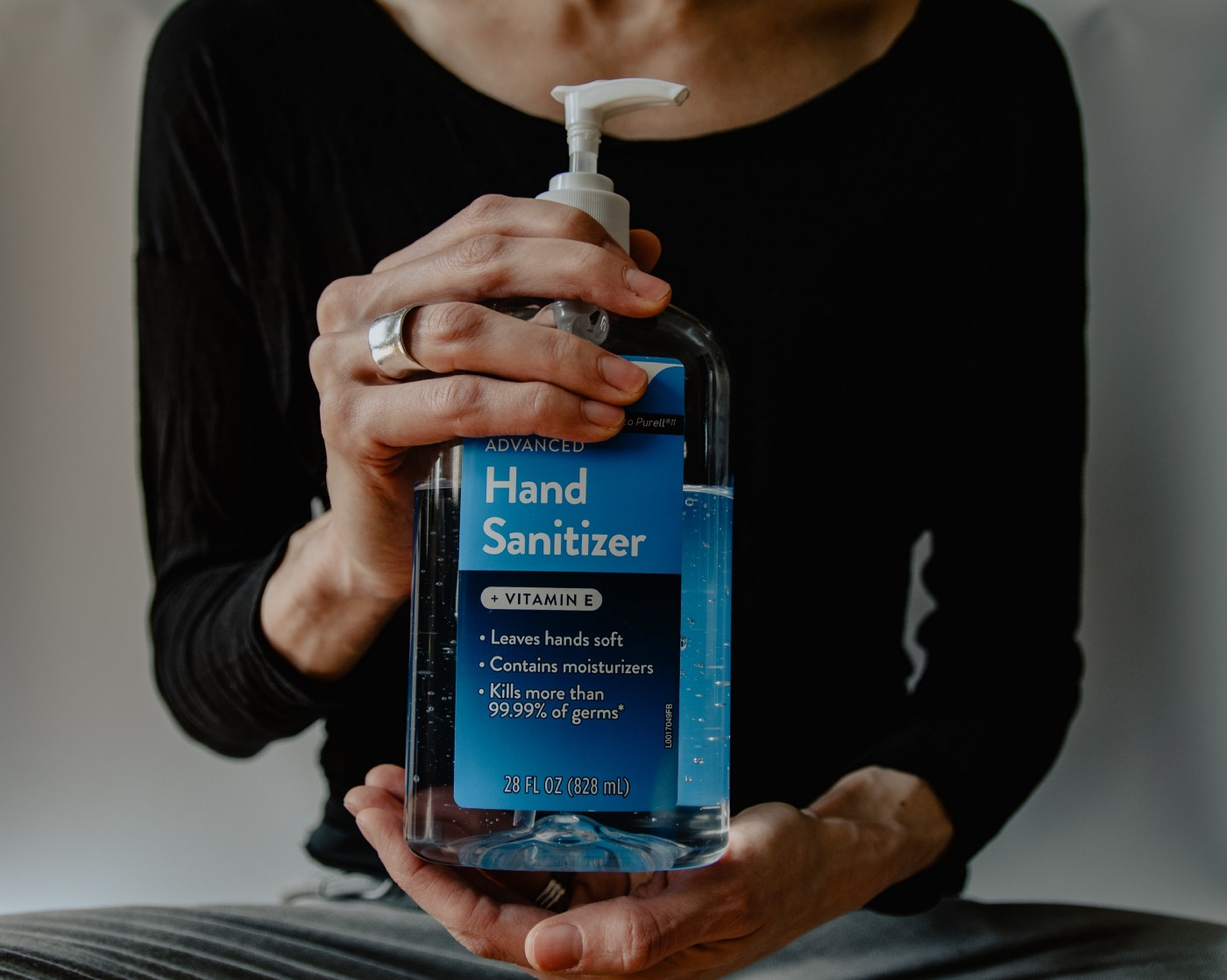 A woman holding a plastic container with hand sanitizer.