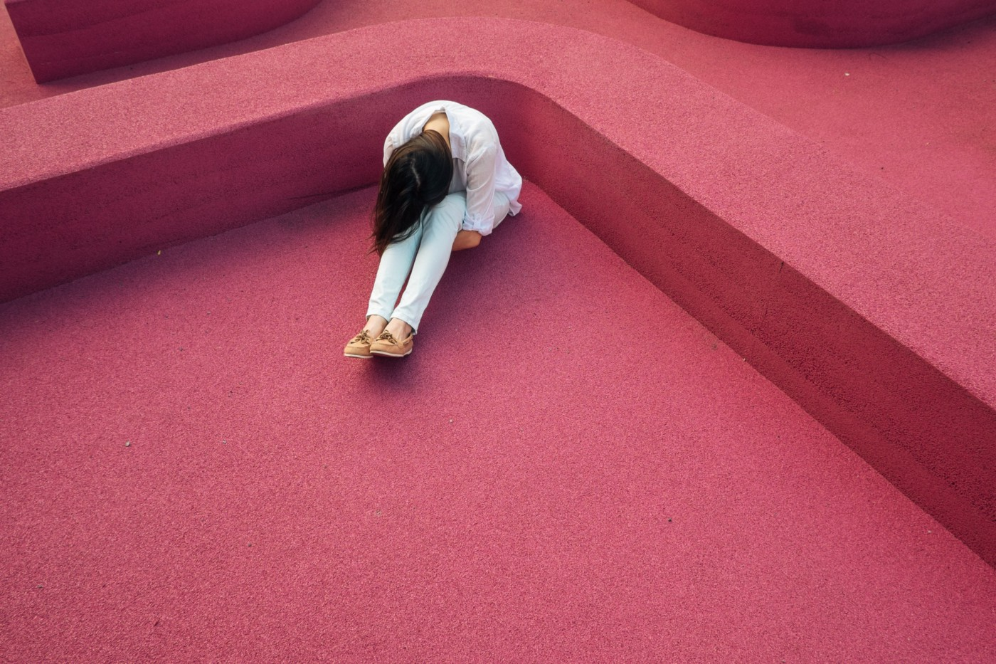 A person bent over with sadness in a pink room.